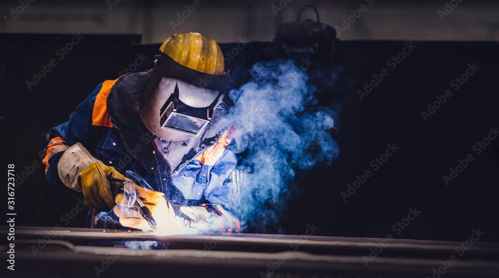 Fototapeta Worker welding in a factory.