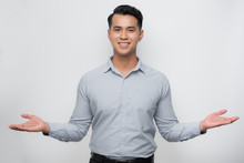 Attractive Young Asian Man Smiling And Welcoming Heartily With Arms Open