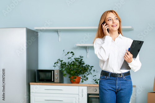 Leinwand Poster Female real estate agent talking by mobile phone indoors