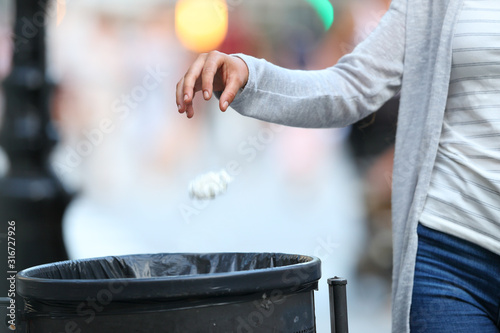 Valokuvatapetti Woman hand throwing garbage to bin at evening