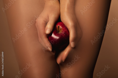 Photo cropped view of woman in nylon tights holding ripe red apple isolated on brown