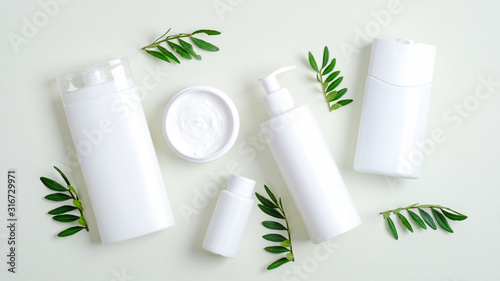 Obraz Set of SPA cosmetic containers and bottles branding mockup and green leaves. Top view shampoo bottle, lotion container, shower gel, essential oil, body cream. Bath beauty products packaging - fototapety do salonu