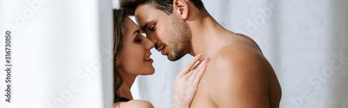 Canvastavla panoramic shot of shirtless man hugging happy woman