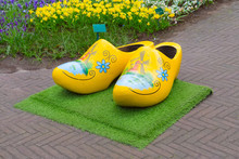 Typical Yellow Dutch Wooden Shoes Clogs Or Klompen, Painted With Windmill And Flowerbed Behind, Netherlands