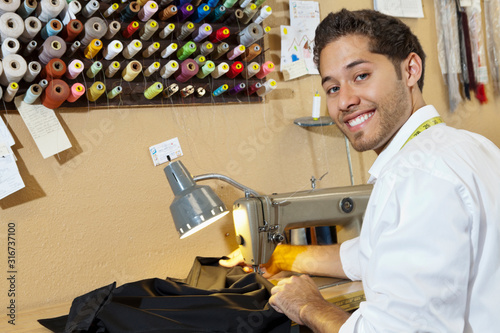 Portrait of young tailor sewing cloth in shop Canvas Print