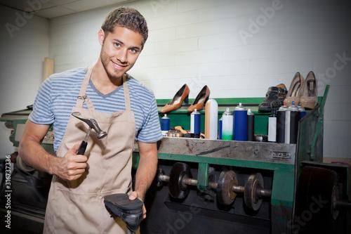 Obraz na plátně Young shoemaker hammering shoe sole in workshop