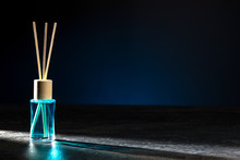 Air Freshener, Reed Diffuser And Aromatherapy Concept - A Bottle Of Home Fragrance Standing On A Stone Countertop On A Beautiful Dark Blue Background. Horizontal.
