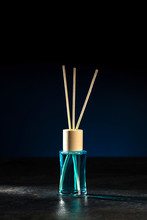 Air Freshener, Reed Diffuser And Aromatherapy Concept - A Bottle Of Home Fragrance Standing On A Stone Countertop On A Beautiful Dark Blue Background. Vertical.