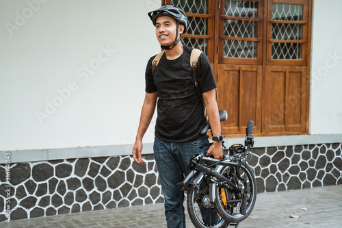 Canvastavla smiling asian young man carrying her folding bike before go in front the house