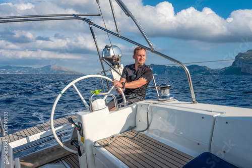 Cuadros en Lienzo Sailor at the helm of modern sailing yacht