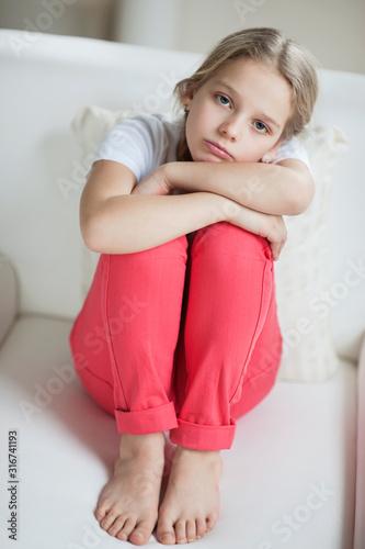 Portret smutny dziewczyny obsiadanie na kanapie