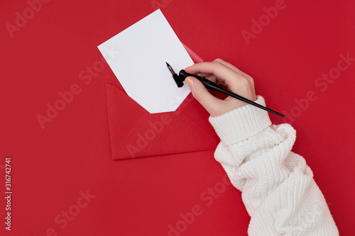 Fényképezés  Woman's hand holding a penholder over an empty mock up postcard in the red envelope on the red background