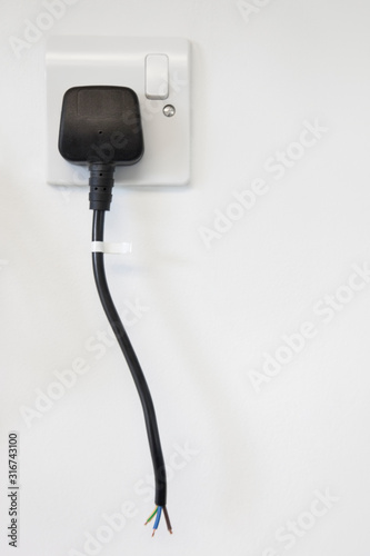 Frayed electrical cord with outlet attached on white wall Wallpaper Mural