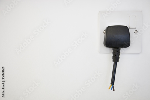 Photo Frayed electrical cord with outlet attached on white wall