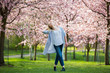 canvas print picture - Young woman enjoying the nature in spring. Dancing, running and whirling in beautiful park with cherry trees in bloom. Happiness concept