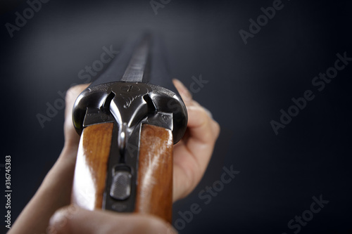 Hand with shotgun on black background. Canvas Print