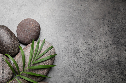 Fotomural Spa stones and palm leaf on grey table, flat lay. Space for text