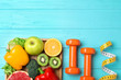 canvas print picture - Fruits, vegetables, measuring tape and dumbbells on light blue wooden background, flat lay with space for text. Visiting nutritionist