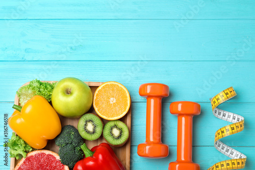 Fruits, vegetables, measuring tape and dumbbells on light blue wooden background, flat lay with space for text Fototapeta