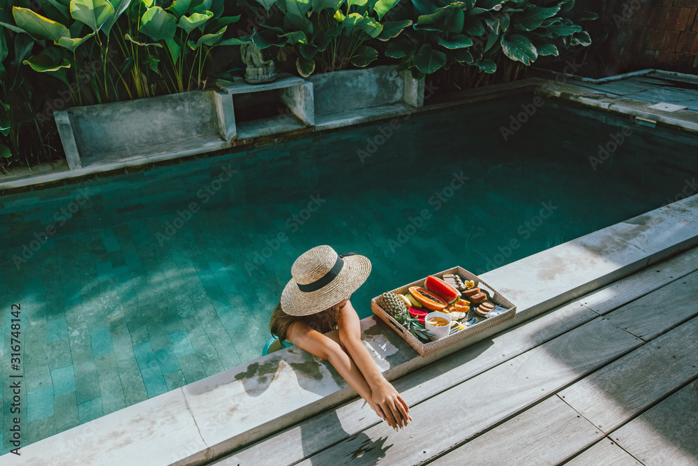 Fototapeta Girl relaxing and eating fruits in the pool on luxury villa in Bali