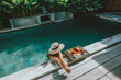 Leinwanddruck Bild - Girl relaxing and eating fruits in the pool on luxury villa in Bali