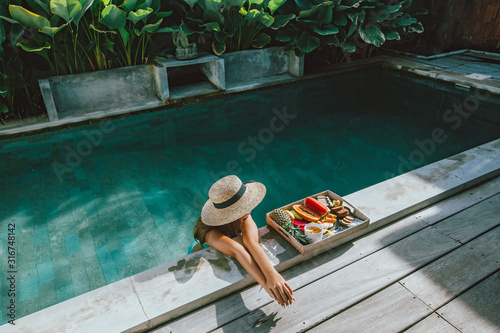 Fotomural Girl relaxing and eating fruits in the pool on luxury villa in Bali