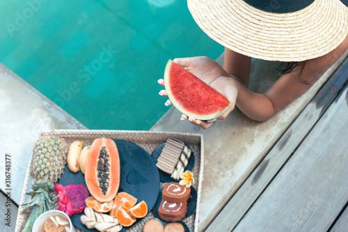 Fototapeta Girl relaxing and eating fruits in the pool on luxury villa in Bali obraz