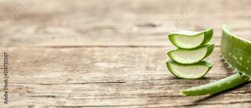 Pieces of aloe vera with pulp on a wooden background