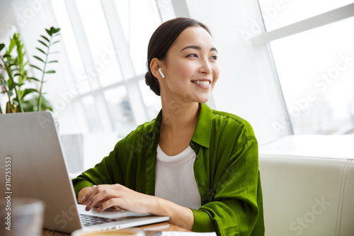 Smiling beautiful young asian woman working on laptop