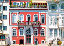 Colorful Red Mansion  With Arched Windows And Beautiful Balconies With Flowers. Classic Architecture Buildings Facades.