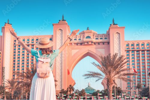 Fototapeta Happy asian girl traveller with backpack enjoying view of the famous luxury Atlantis hotel building on a Jumeirah Palm Island in Duba, UAE obraz
