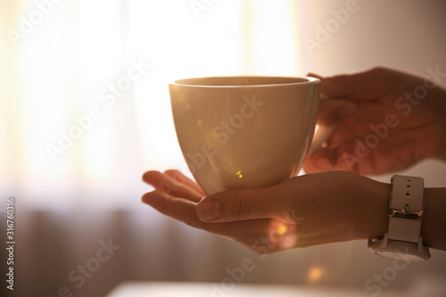 Obraz Woman holding cup of drink on blurred background, closeup. Lazy morning - fototapety do salonu