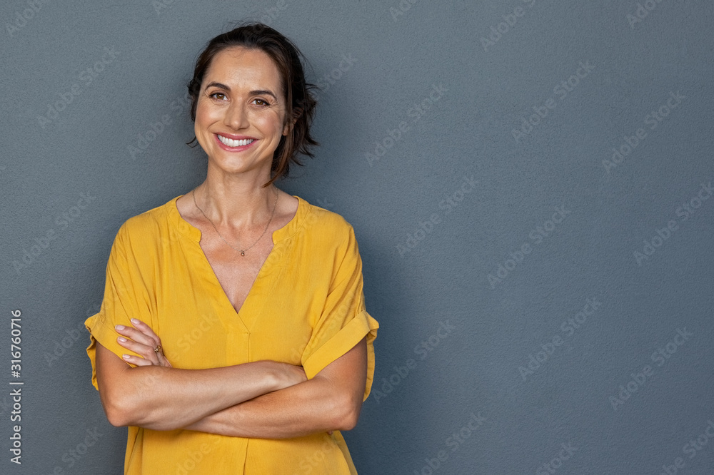 Fototapeta Happy mature woman smiling on grey wall