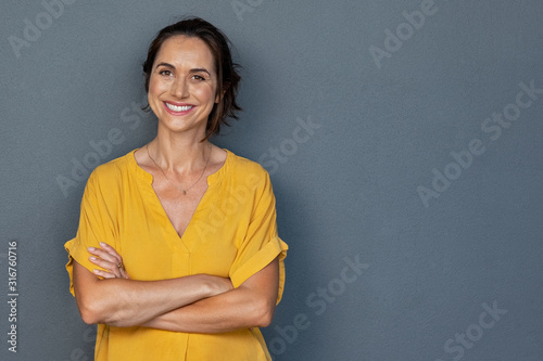 Happy mature woman smiling on grey wall - 316760716
