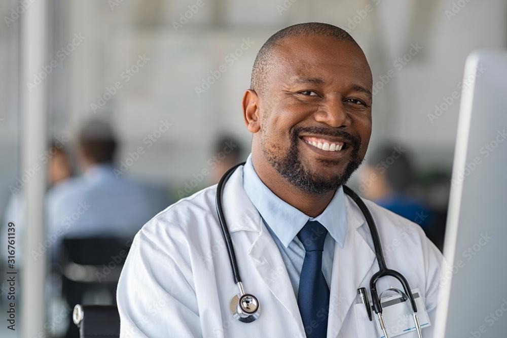 Fototapeta Happy smiling black doctor looking at camera