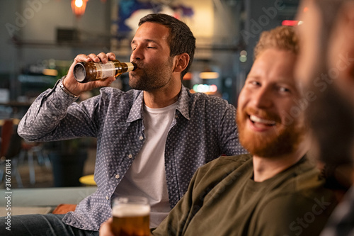 Man with friends drinking a bottle of beer
