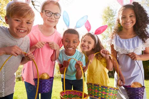 Photo Portrait Of Five Children Wearing Bunny Ears On Easter Egg Hunt In Garden