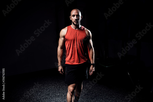 Strong muscular bodybuilder athletic man looking at camera while standing on dark studio Wallpaper Mural