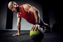 Muscular Young Man Doing Push Ups With Medicine Ball On Dark Studio.
