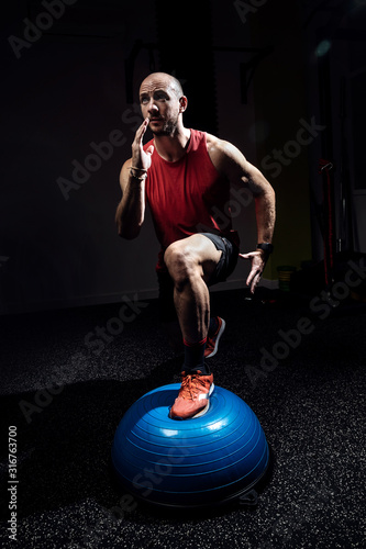 Fototapeta Fit athlete performing exercise on gymnastic hemisphere bosu ball on dark studio. obraz