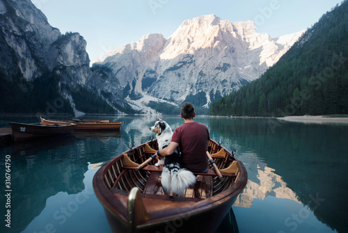 Photo man and dog in a boat on a mountain lake