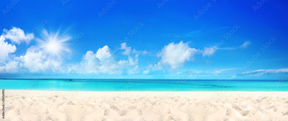 Fototapeta Beautiful beach with white sand, turquoise ocean water and blue sky with clouds in sunny day. Panoramic view. Natural background for summer vacation.