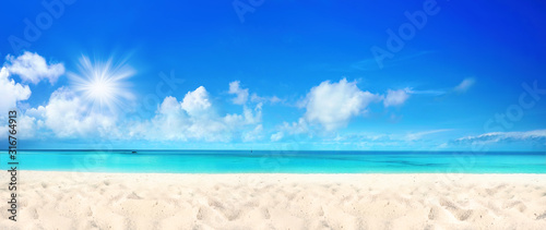 Obraz Beautiful beach with white sand, turquoise ocean water and blue sky with clouds in sunny day. Panoramic view. Natural background for summer vacation. - fototapety do salonu