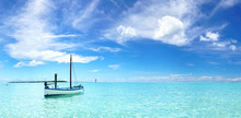 Boat In Turquoise Ocean Water Against Blue Sky With White Clouds. Natural Landscape For Summer Vacation.