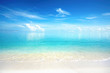 Leinwanddruck Bild - Beautiful sandy beach with white sand and rolling calm wave of turquoise ocean on Sunny day. White clouds in blue sky are reflected in water.  Maldives, perfect scenery landscape, copy space.