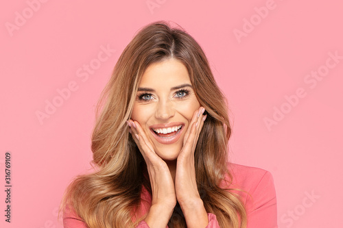 Happy smiling woman on pink background. Fototapet