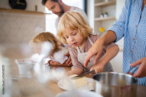 Fotografía Young family with two small children indoors in kitchen, preparing food