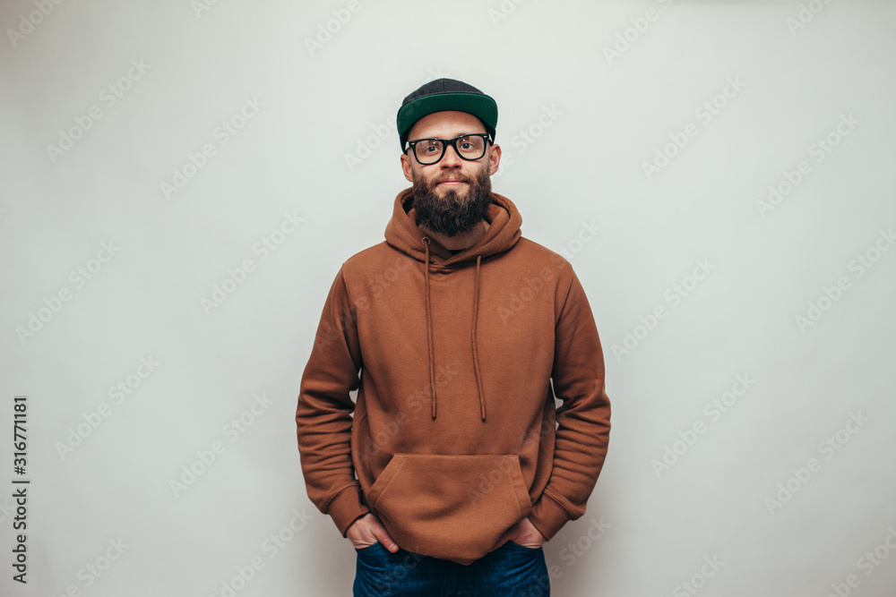 Fototapeta Handsome hipster guy with beard wearing brown blank hoodie or hoody and black cap with space for your logo or design on white background. Mockup for print