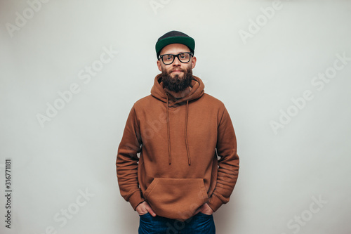 Handsome hipster guy with beard wearing brown blank hoodie or hoody and black cap with space for your logo or design on white background Canvas Print