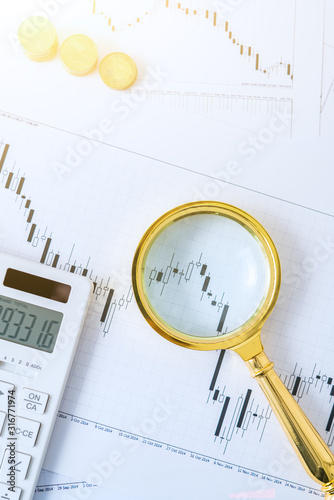 Calculator, magnifying glass, coins and pen on a bar chart-stock finance concept image - 316771974